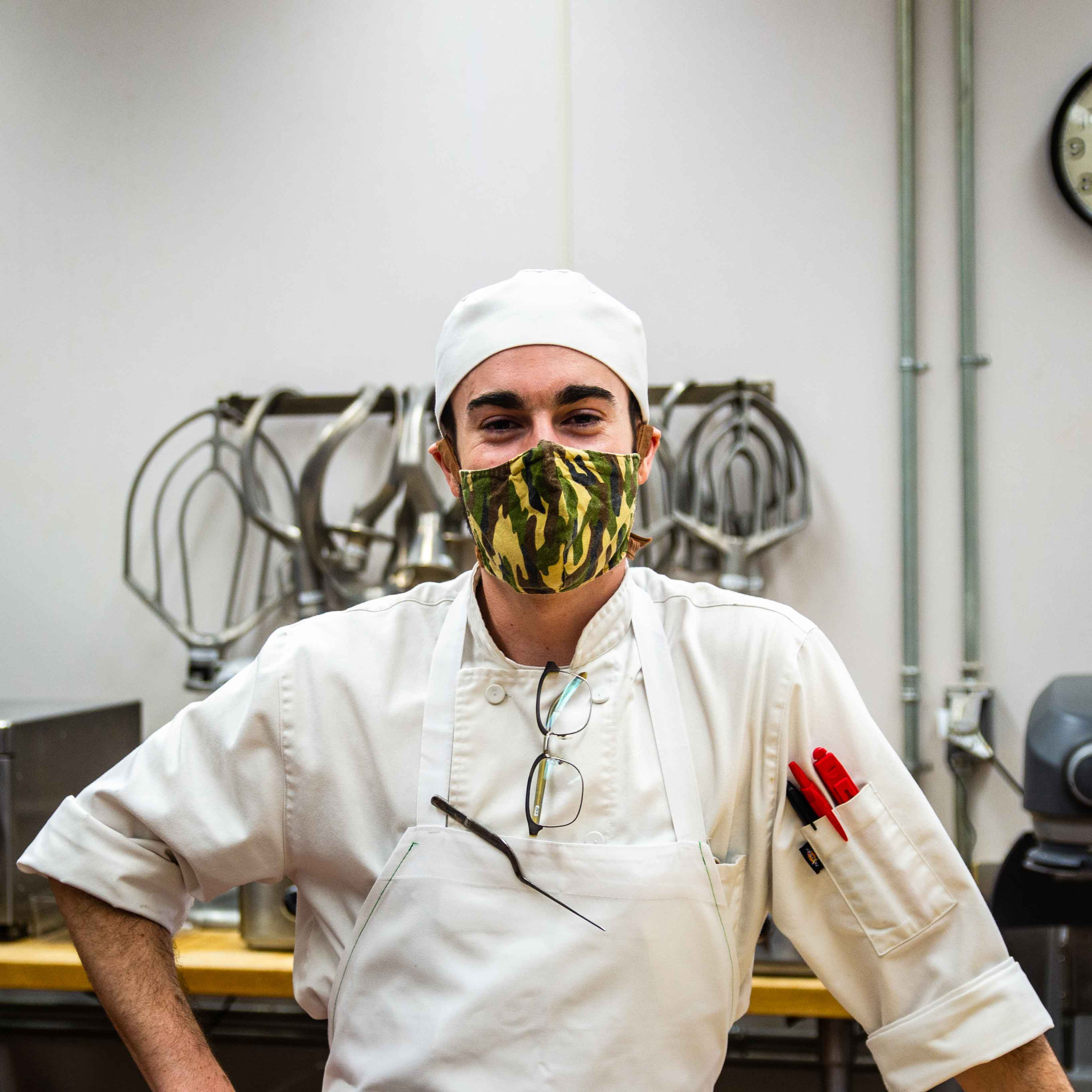 Student in white chef's clothes and masks poses in kitchen