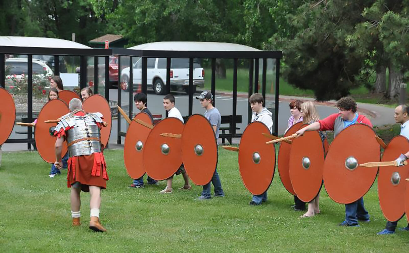 Students hold shields outside for Medieval reenactment