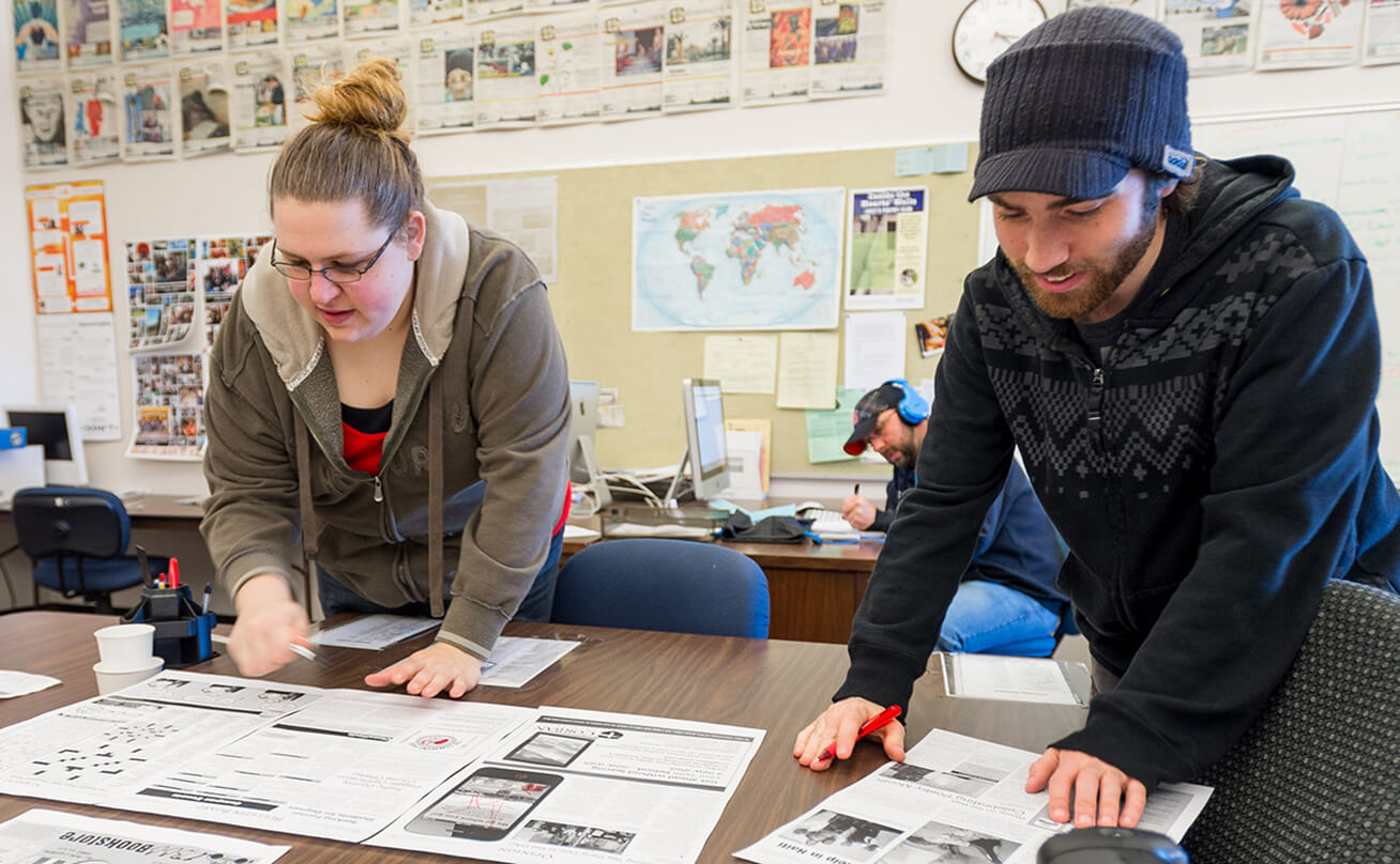 Female and male students working on newspaper layout in classroom