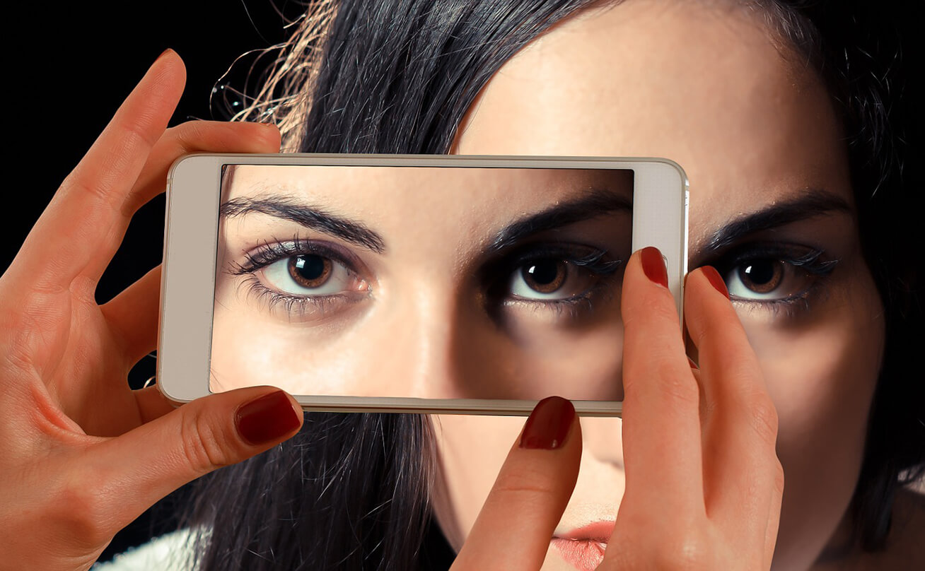 Woman looking at cell phone camera with her eyes reflected back