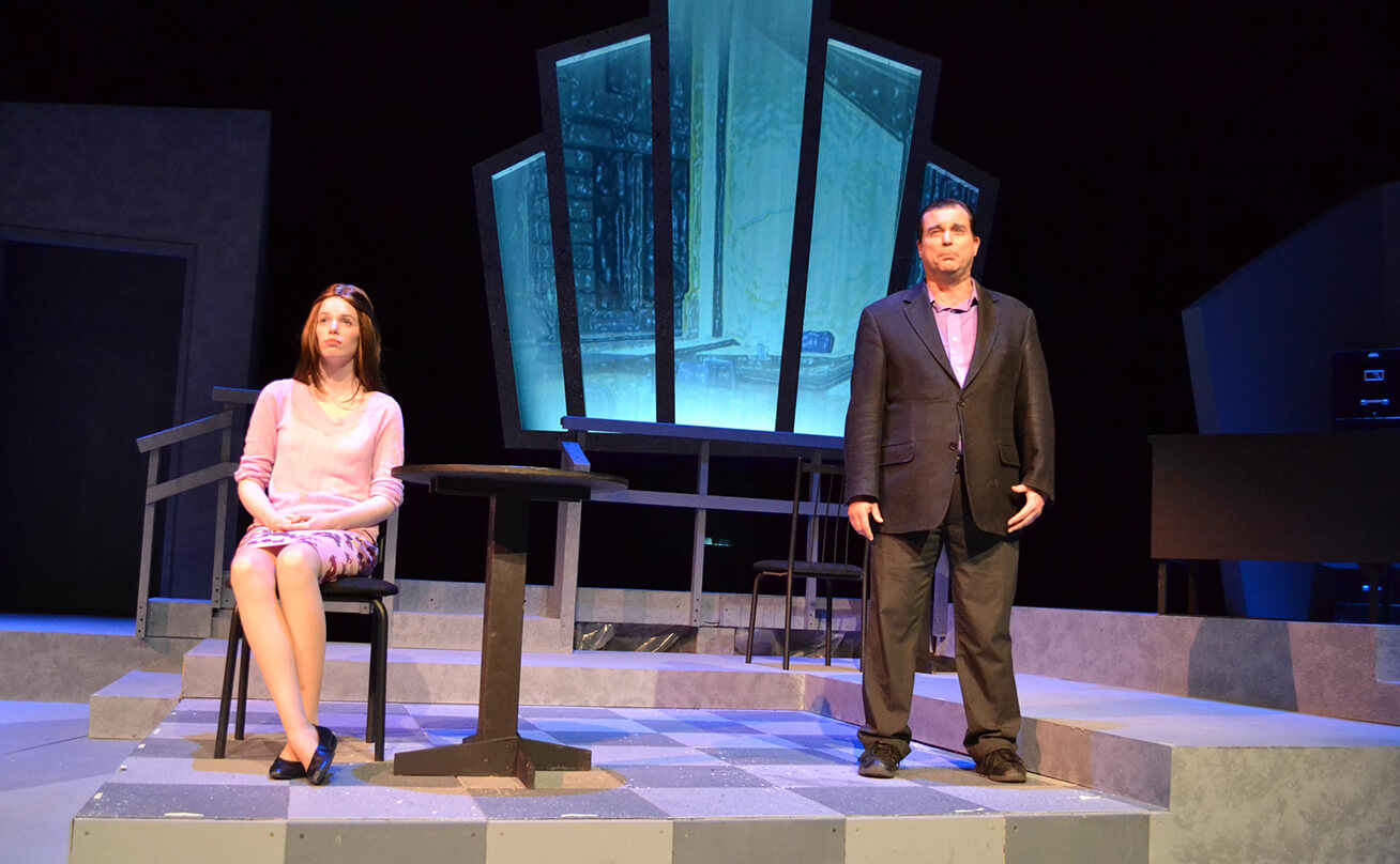 Woman sitting in a chair and man standing in a suit on stage during a play