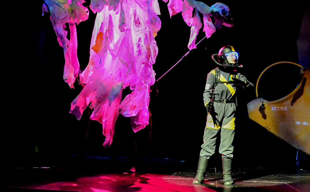 Female actor on stage in a spacesuit