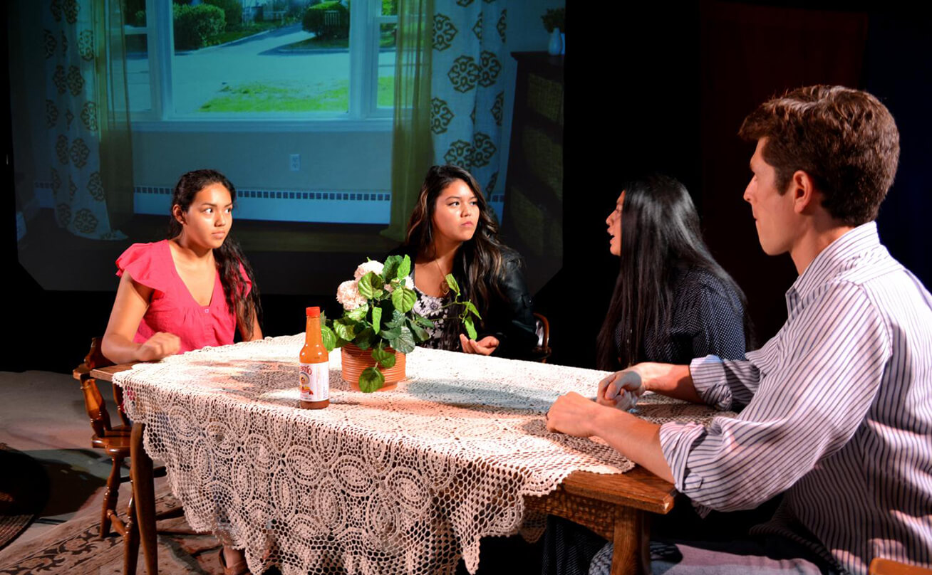 Four students tensely sitting at a table in a play