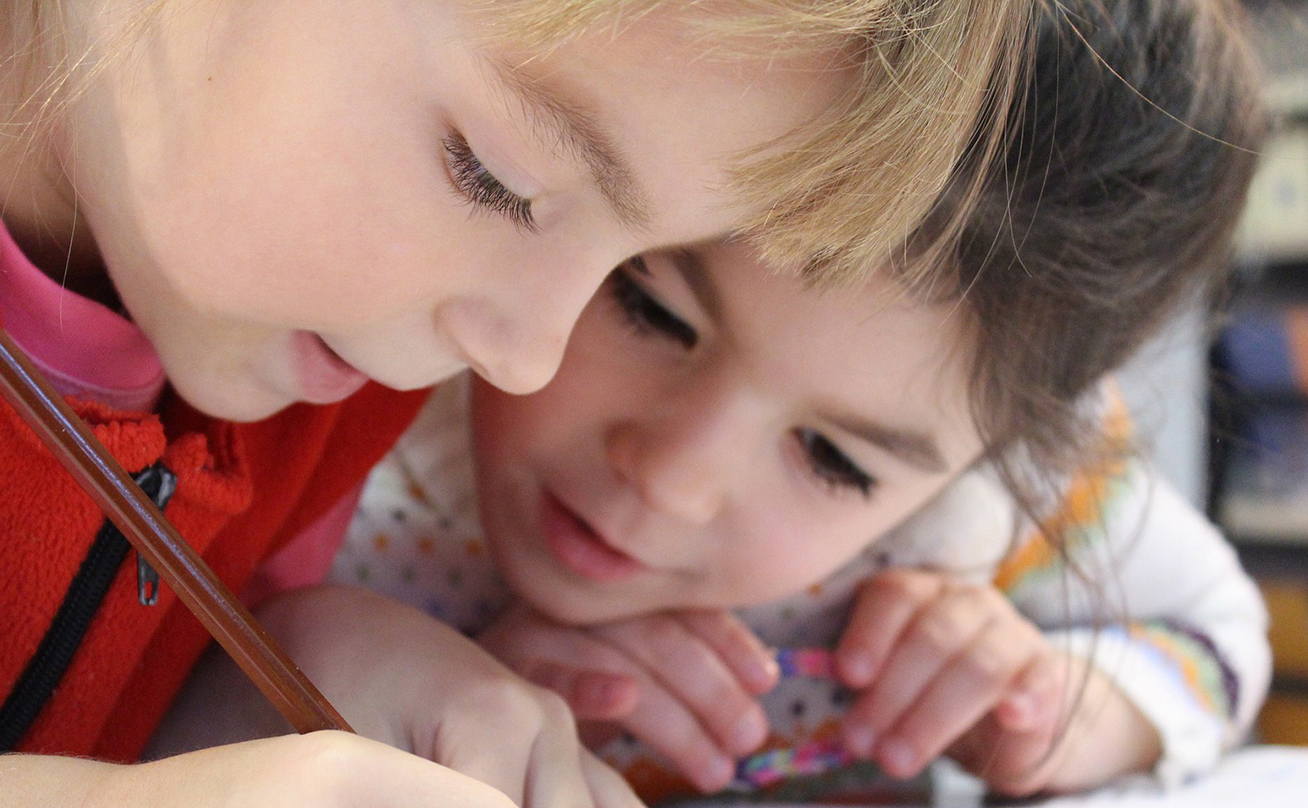 Close up view of two children drawing together