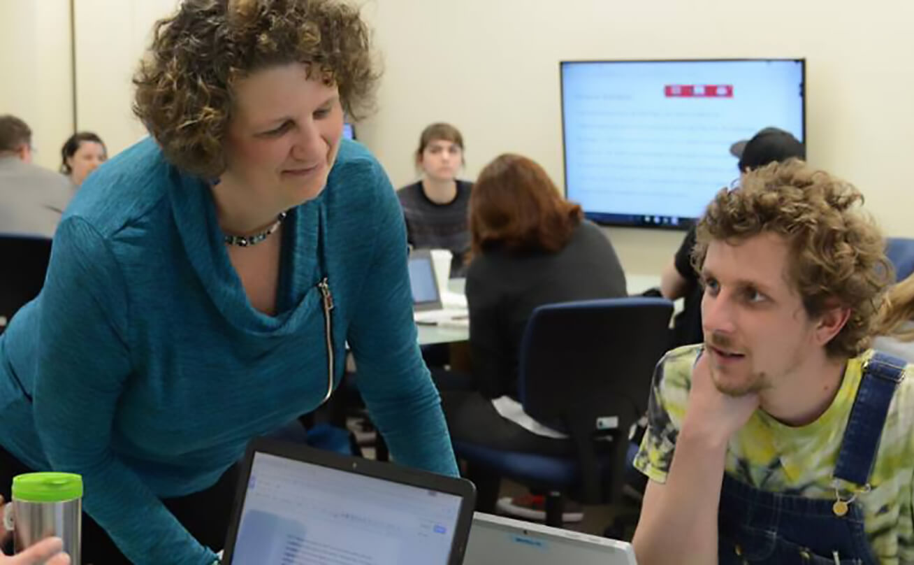 Professor leans over table to help student in LBCC classroom