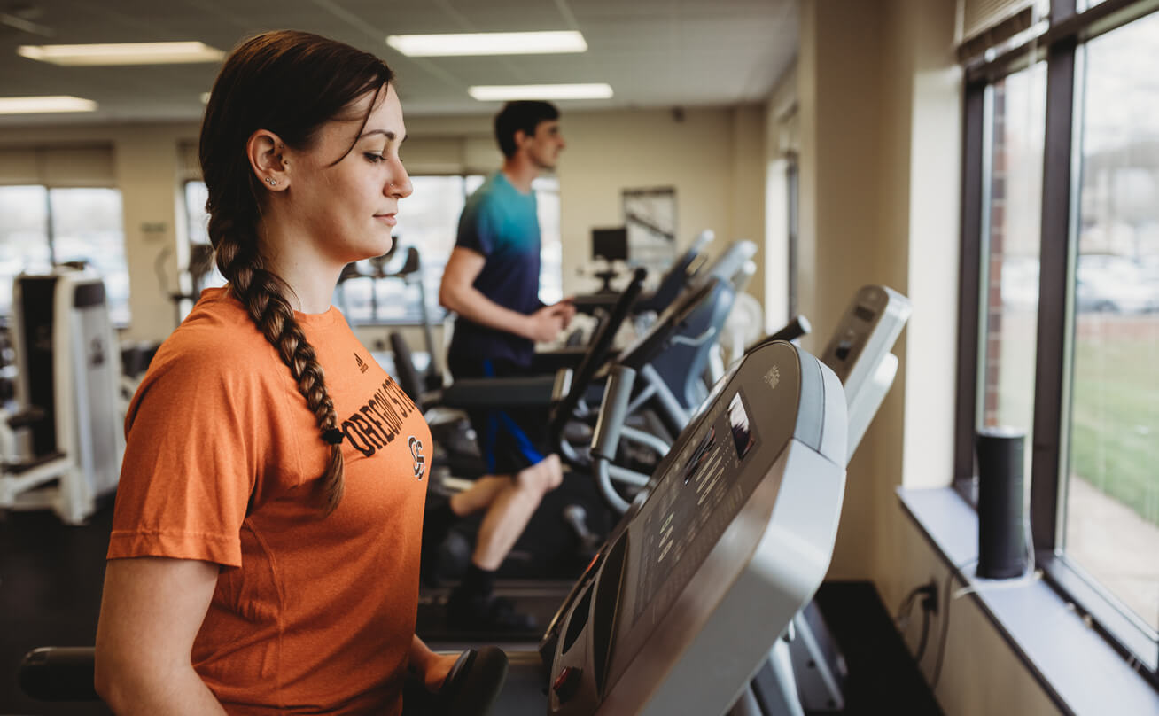 Woman walking on treadmill with Oregon State t-shirt