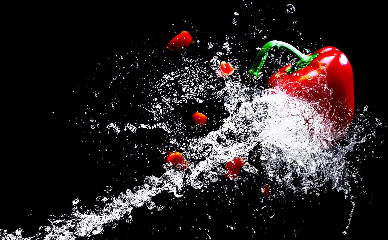 Red bell pepper being hit with jet of water